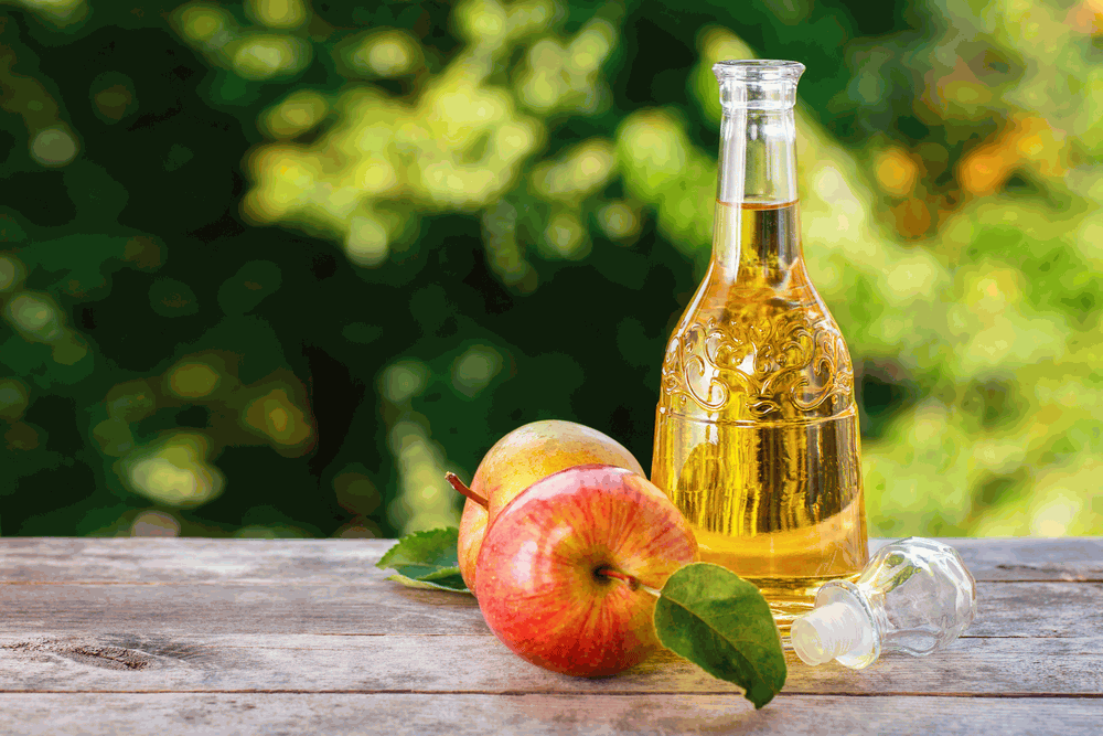 cider vinegar in glass decanter and ripe fresh apples