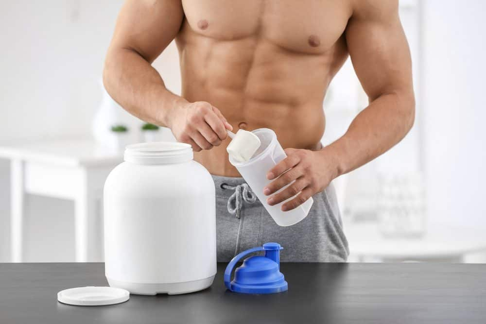 Young sporty man preparing protein shake
