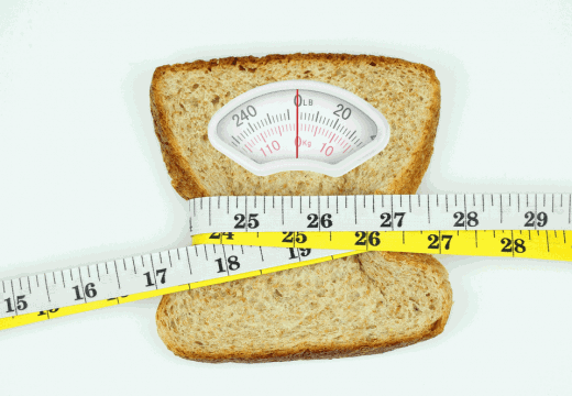 Weight scale with wholesome slice of bread and measuring tape